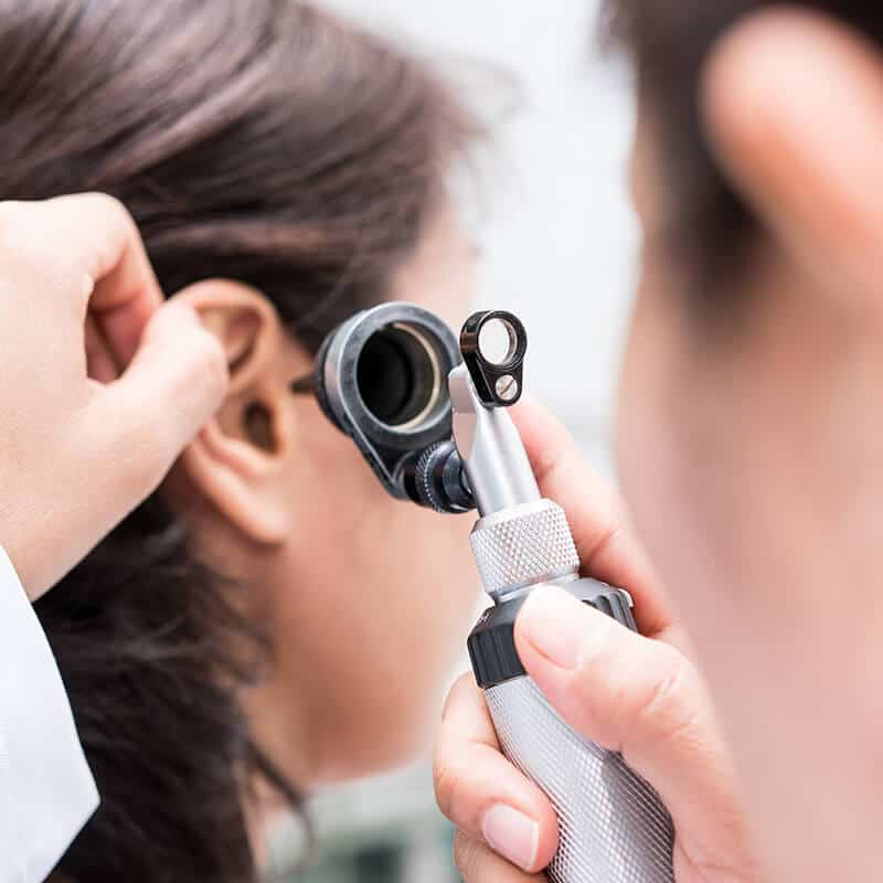 checking ear with otoscope