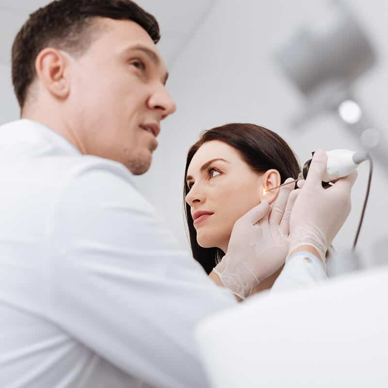 audiologist checking a patient's ear